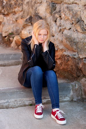 girl sitting down: Cool blonde girl sitting outdoor looking down
