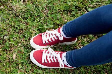 treading: With red sneakers and jeans in the field treading the grass Stock Photo