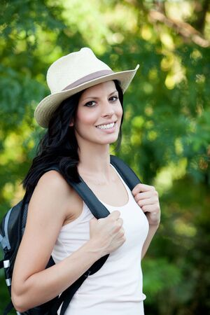 chapeau paille: Brunette woman with straw hat walking through the woods Banque d'images