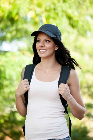 ooking: Beautiful brunette woman with cap and backpack hiking Stock Photo