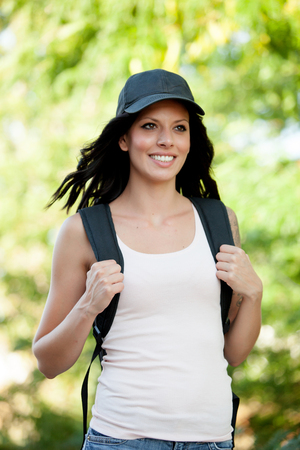 Beautiful brunette woman with cap and backpack hiking Stock Photo