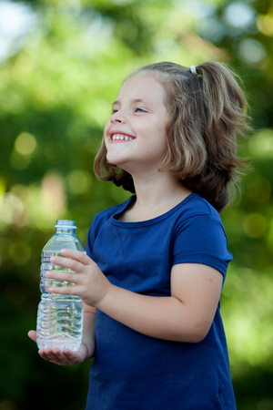 Cute little girl with water bottle in the park