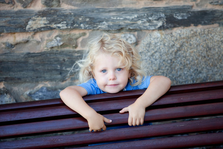 curly hair child: Little child three year old with blond curly hair hidden behind a wooden bench