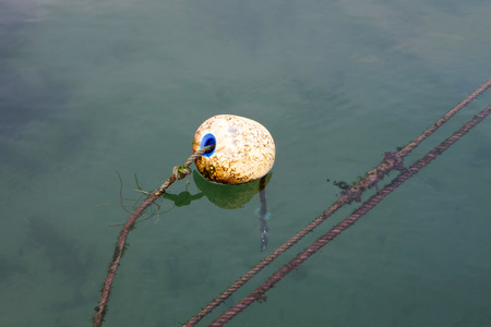 Dirty round buoy in the sea to signal Stock Photo