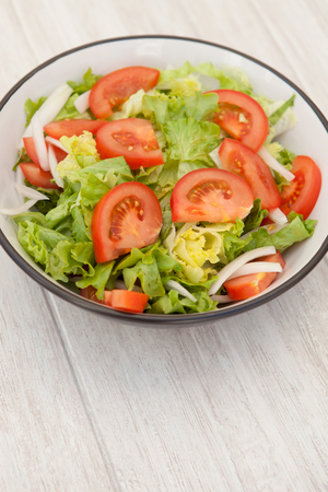 tomate ensalada: Salad bowl with lettuce tomato and onion on a white wooden background Foto de archivo