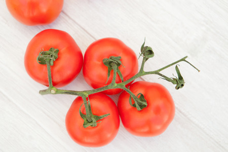 Bright picture of vine tomatoes on a white wooden background Stock Photo