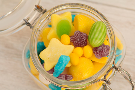 Container glass filled with candies on a gray wooden background