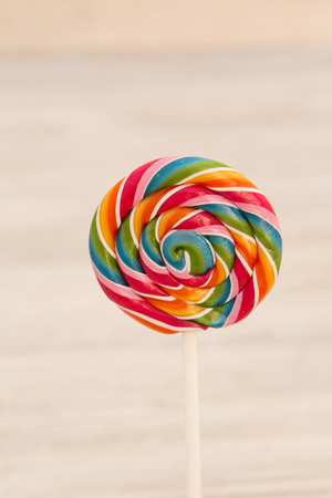 Nice round lollipop with many colors in a spiral on a wooden background Stock Photo