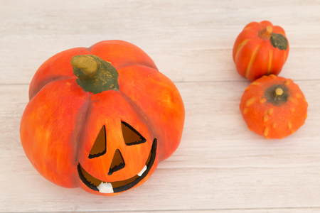 Orange pumpkin lantern with a spooky face smiling on a wooden grey background Stock Photo