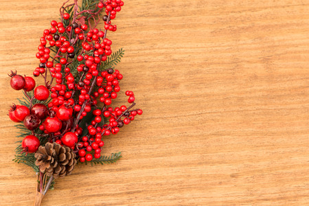 Red fruits on the branch Christmas for decoration on a wooden background Stock Photo