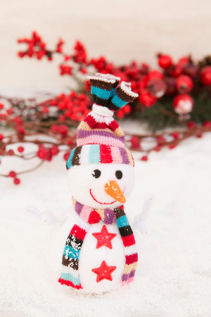 fact: Snowman made of wool over the snow with a branch of red berries background. Christmas decoration