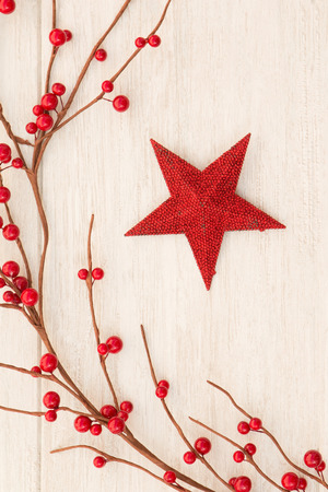 red berries: Red Christmas star on gray wooden background decorated with red berries