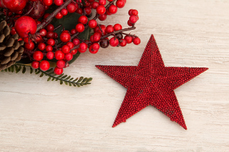 red berries: Red Christmas star on gray wooden background and red berries