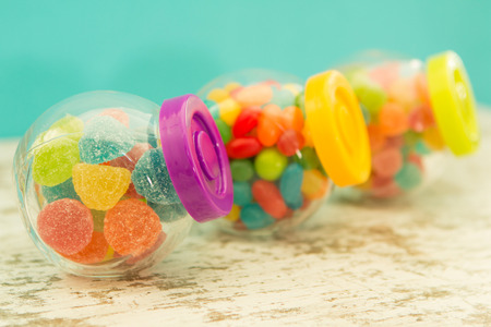 glass containers: Three glass containers full of jellybeans on wooden table with blue background. Focus in the foreground