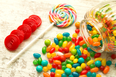 jelly beans: Glass bowl fallen with colorful jelly beans and a lollipop