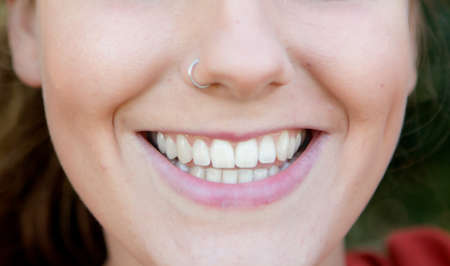 Portrait of beautiful young woman smiling closely with pirsing on her nose Stock Photo