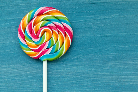 Nice lollipop with many colors in a spiral on a wooden background