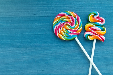 Two lollipops with many colors in a spiral on a wooden background Stock Photo