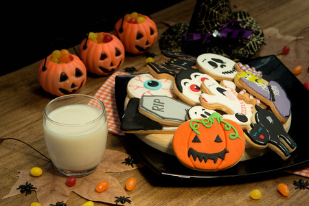Creepy Halloween cookies next to a milk glass on a wooden table