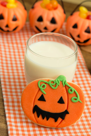 Creepy Halloween cookie next to a milk glass on a wooden table