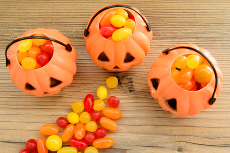 Halloween pumpkin baskets full of candies on a wooden background Stock Photo