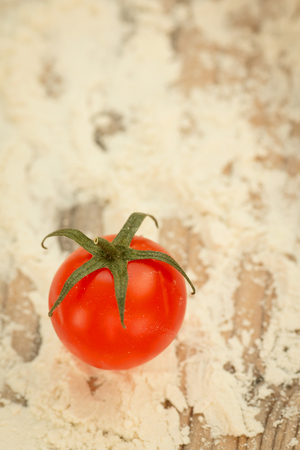 Small cherry tomato on a table smeared with flour. Ingredient for the sauce