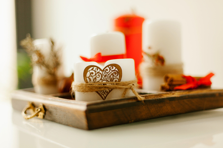 Wooden tray with candles decorated with a heart