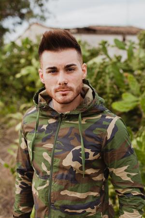 militaire sexy: guy Attractive avec la veste militaire et les plantes de fond