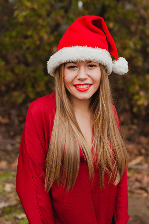 misterious: Young woman with Christmas hat and red lips in the forest