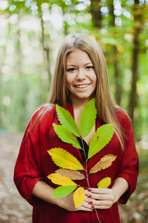 misterious: Blonde girl in a misterious forest holding a branch of a tree with autumn colors