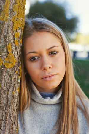 leafed: Pretty blonde girl in the park looking at camera Stock Photo