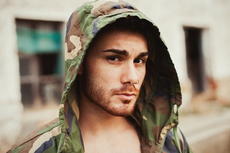 fashion clothing: Hooded guy with camouflage jacket in the street