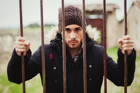 Attractive guy behide the bars with a wool hat