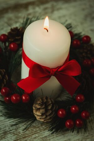 corona navidad: Burning candles in a Christmas wreath with seasonal decorations. Foto de archivo