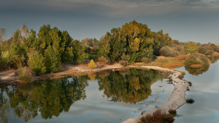 dyllic: Beautiful scenery of the banks of a river with trees reflected in water Stock Photo