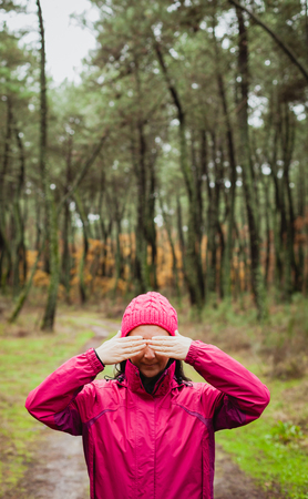 Woman with pink wool hat in the forest covering her eyes Stock Photo