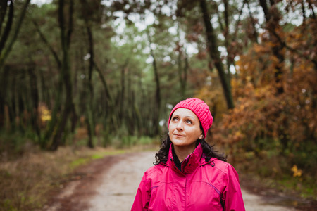 misterious: Matured woman with wool pink hat in the forest