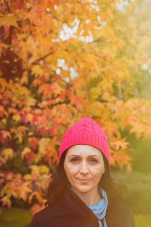 Matured woman with pink wool hat in the forest photo