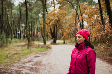 Matured woman with wool pink hat in the forest photo