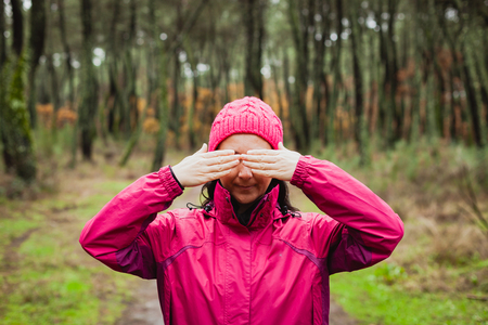 Woman with pink wool hat in the forest covering her eyes photo