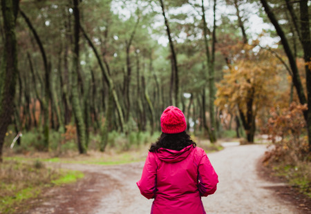 misterious: Matured woman hiking in the forest at winter