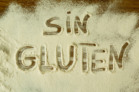 coeliac: Flour on the table with writted word GLUTEN Stock Photo