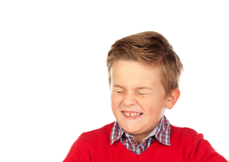 Blond child with a funny expression closing his eyes isolated on a white background Stock Photo