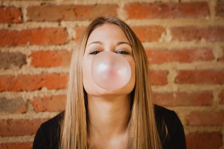 pomp: Funny girl making a pomp with a bubble gum and a brick wall of background