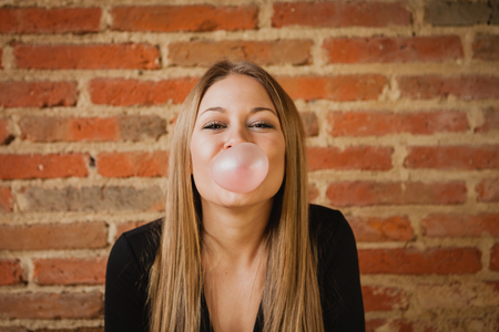 Funny girl making a pomp with a bubble gum and a brick wall of background