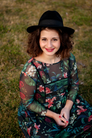 flowered: Beautiful girl with flowered dress an black hat in the landscape Stock Photo