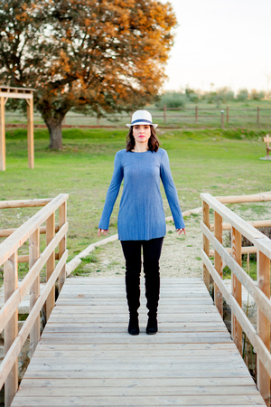whithe: Stylish young woman with whithe hat on a wooden bridge in the field