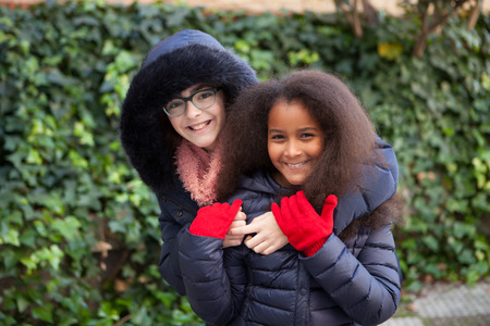 Two happy girls in the park with coats