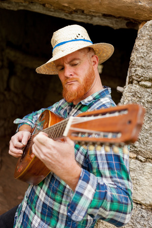 Hipster man with red beard playing the guitar in a rural enviroment Stock Photo