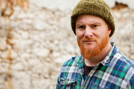 Red haired man with plaid shirt with a old wall with background